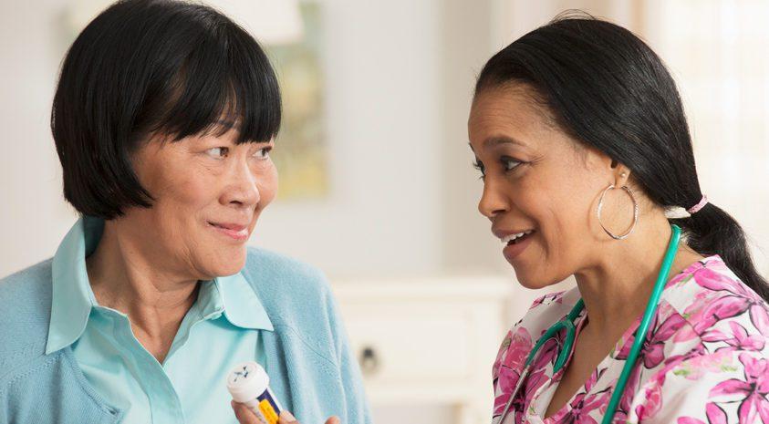 Retiree-and-long-term-care-nurse-discuss-care