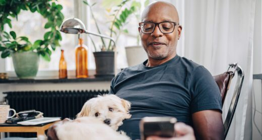 Man reading phone with dog in his lap