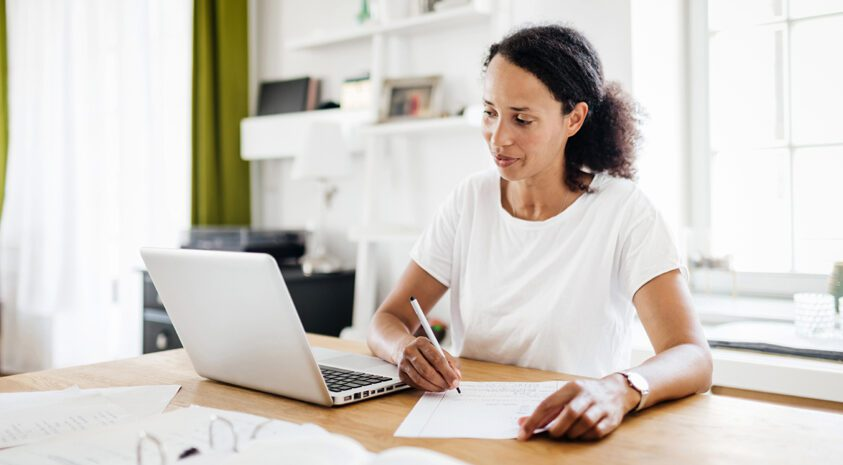 woman taking notes from laptop